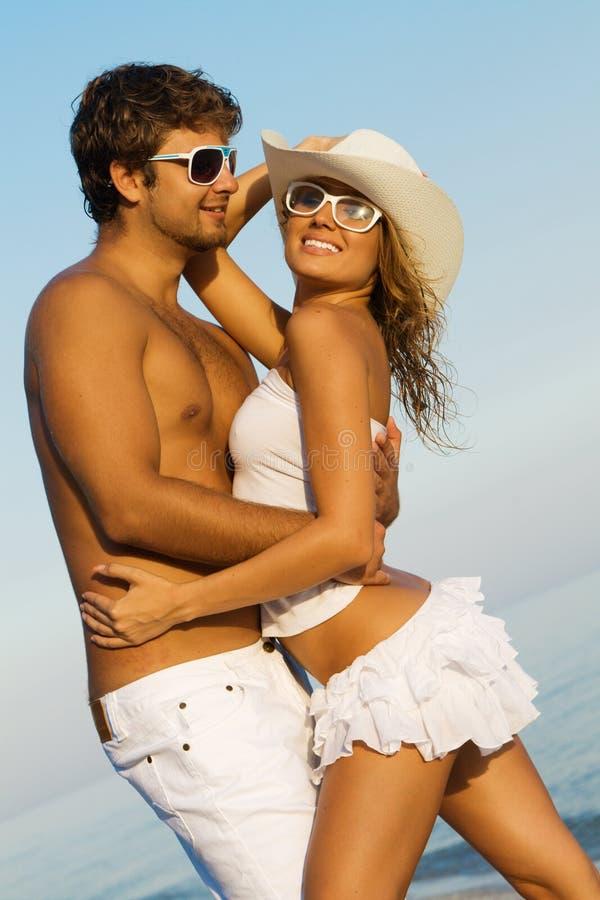 Junge stilvolle Paare auf einem Seeufer stockbilder