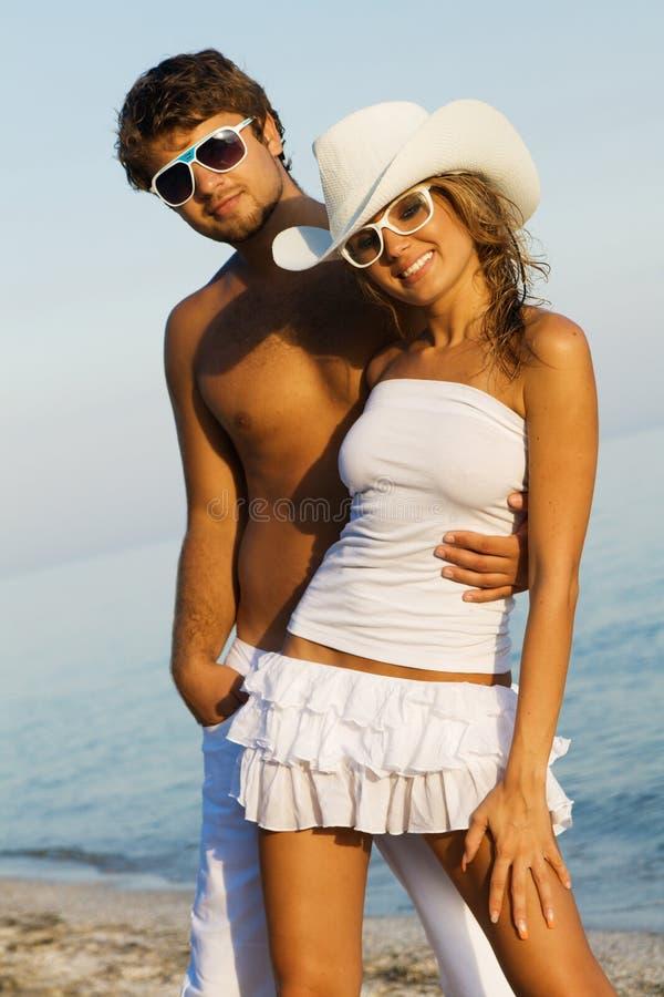Junge stilvolle Paare auf einem Seeufer lizenzfreie stockbilder