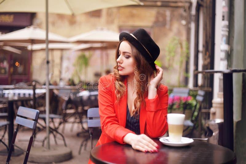 Junge stilvolle Schönheit, die im Stadtcafé in der roten Jacke, Straßenart, trinkender aromatischer Kaffee sitzt Elegantes Mädche lizenzfreie stockfotos