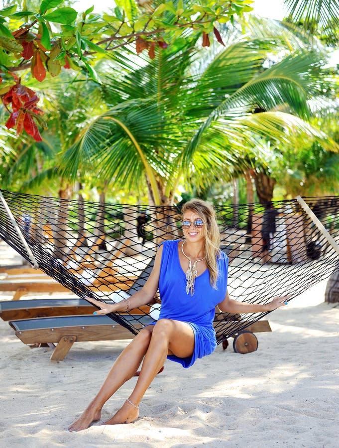 Junge stilvolle Schönheit im blauen Kleid- und Sonnenbrille Layin lizenzfreies stockfoto