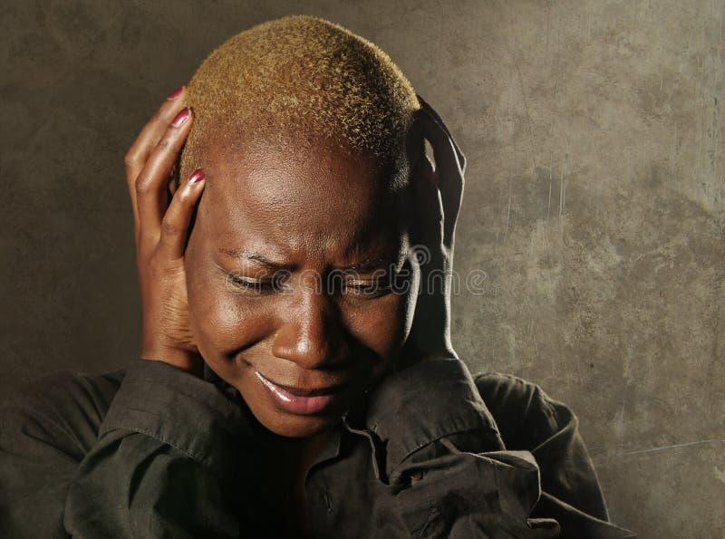 Junge stilvolle traurige und deprimierte afroe-amerikanisch schwarze Frau, die in der Verzweiflung halten Haupt mit den Händen si stockbild