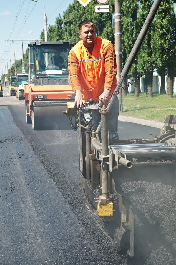 Junge Straßenbetoniermaschinearbeitskraft an der Asphaltierung stockfoto