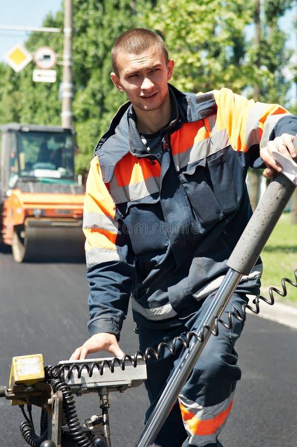 Junge Straßenbetoniermaschinearbeitskraft an der Asphaltierung lizenzfreie stockfotografie