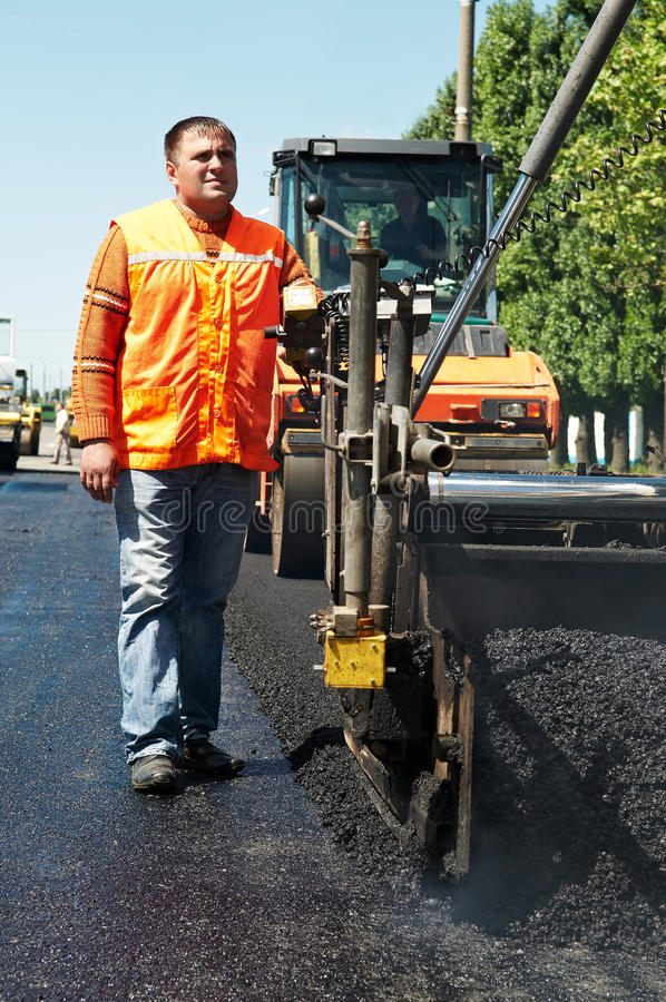 Junge Straßenbetoniermaschinearbeitskraft an der Asphaltierung lizenzfreies stockbild
