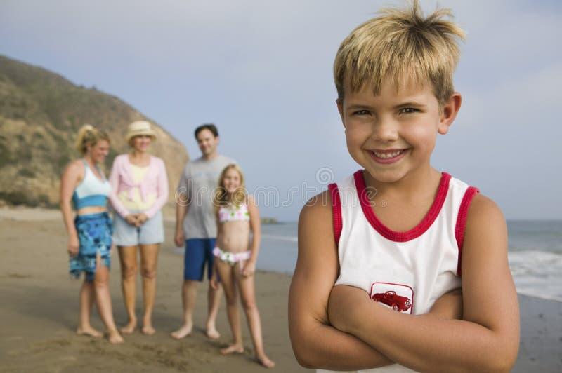 Junge am Strand mit seiner Familie im Hintergrund stockfoto