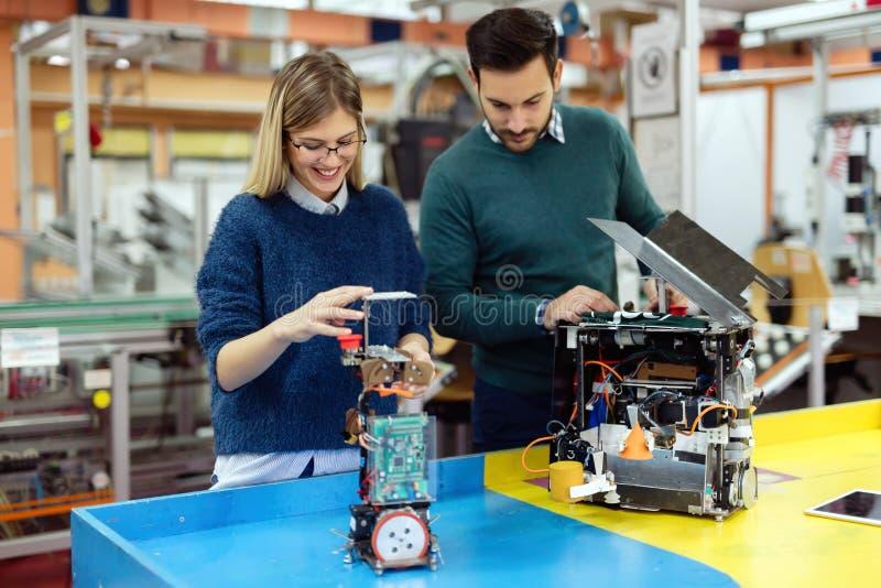 Junge Studenten der Robotik Roboter für die Prüfung vorbereitend lizenzfreie stockfotos
