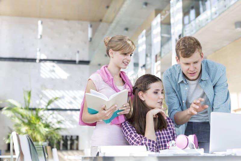 Junge Studenten, die über Laptop bei Aufgabe bei Tisch machen in der Universität sich besprechen lizenzfreie stockfotos
