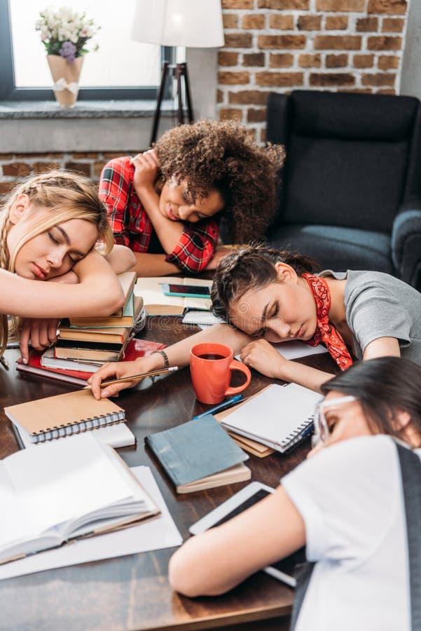 Junge Studenten, die auf Tabelle mit Notizbüchern und digitalen Geräten schlafen lizenzfreie stockbilder