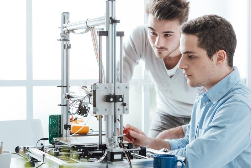 Junge Studenten, die einen Drucker 3D verwenden lizenzfreie stockfotos