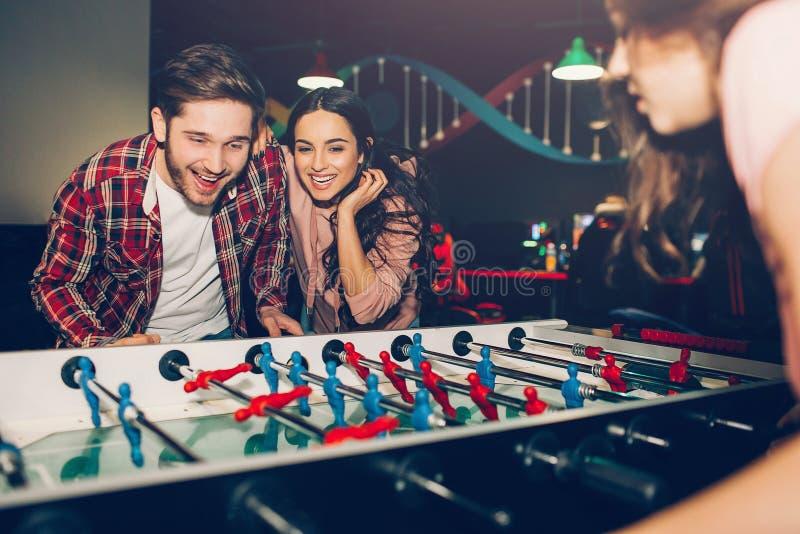 Junge Studenten, die zusammen Tabellenfußball im Raum spielen Manngegner zur Frau Sie aufgeregt und spielerisch lizenzfreies stockbild