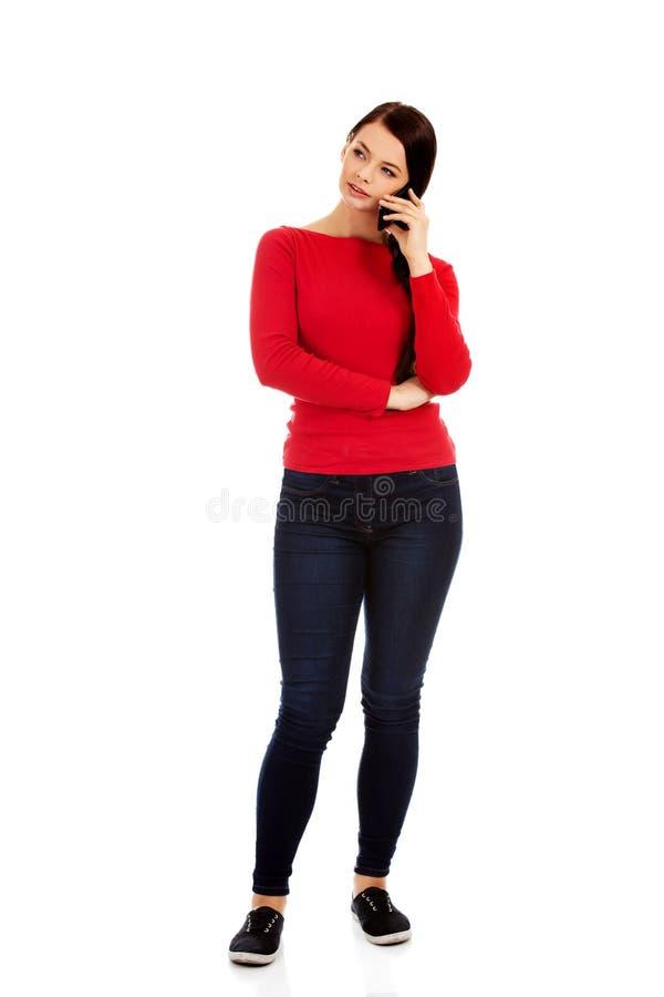 Junge Studentenfrau, die durch einen Handy spricht stockbild