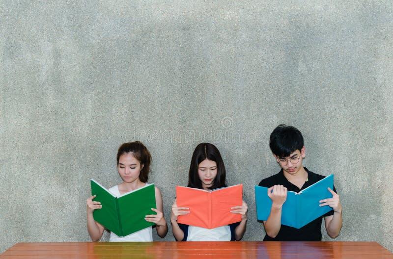 Junge Studentengruppe ernste Ablesenschule, die Ordner buchen stockbilder