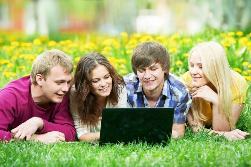 Junge Studentengruppe mit Computer draußen stockbilder