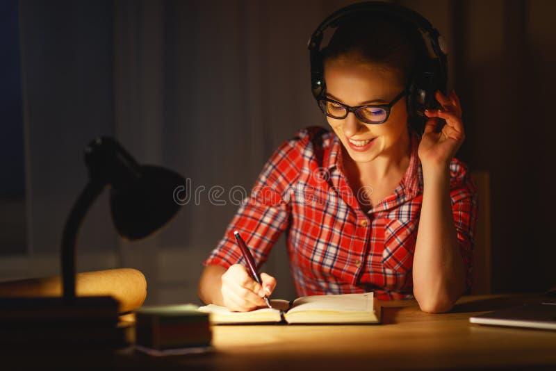 Junge Studentin in den Kopfhörern, die an dem Computer am nig arbeiten stockbilder
