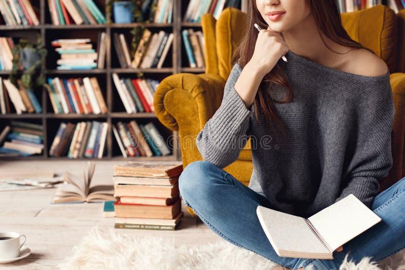 Junge Studentin in der Bibliothek zu Hause, die das Träumen sitzt stockbilder