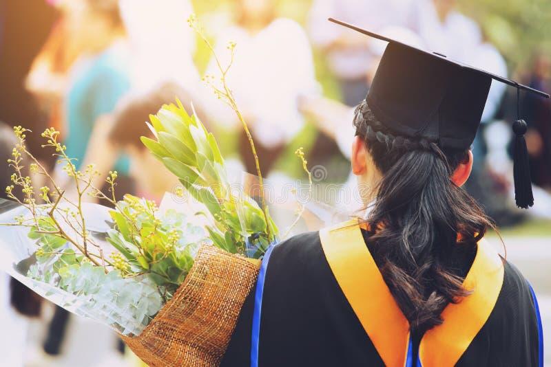 Junge Studentin der Rückseite des Schusses in der Hand, die einen Blumenstrauß von Blumen die Absolvent von Staffelungshüten hält lizenzfreie stockfotos