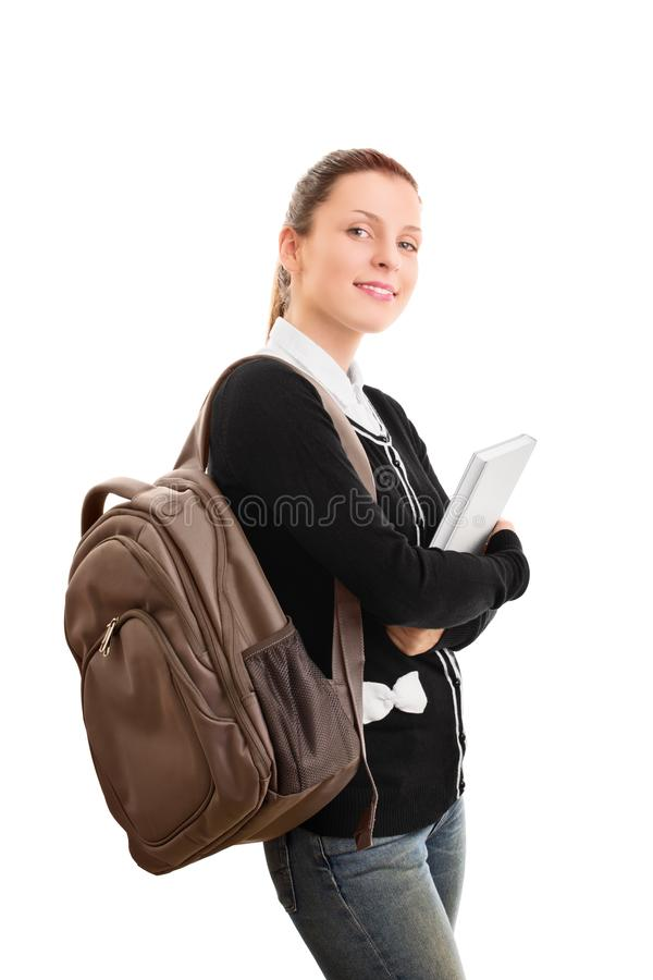 Junge Studentin mit einem Rucksack, der ein Buch hält lizenzfreies stockbild