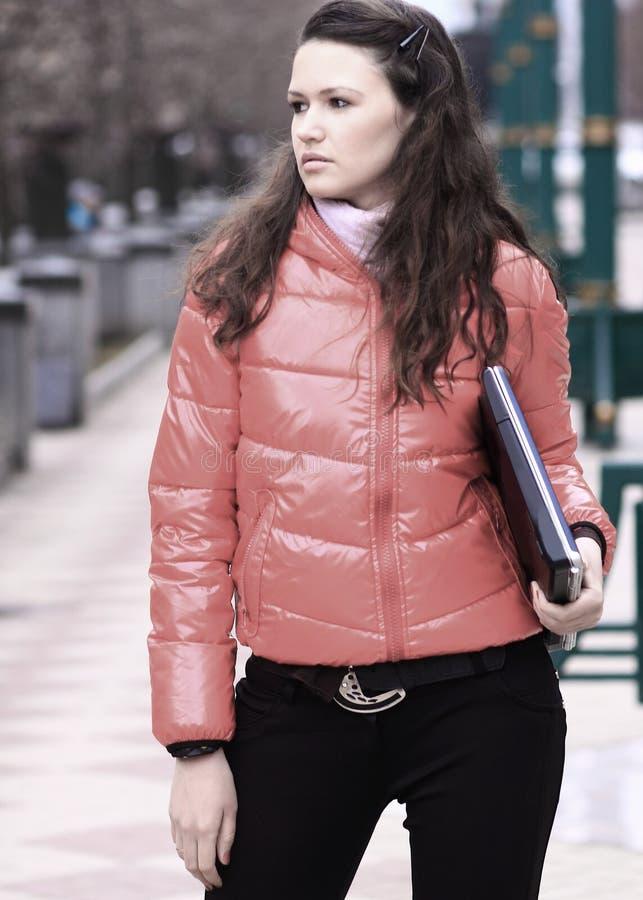 Junge Studentin mit Laptop auf dem Hintergrund einer Winterstadt lizenzfreie stockfotografie