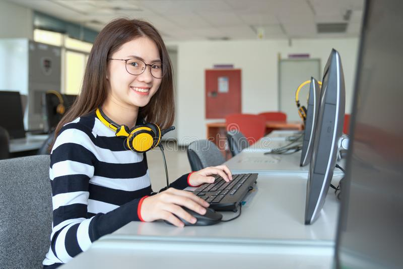 Junge Studentinstudie in der Schulbibliothek, sie unter Verwendung des Laptops und online lernen, zurück zu Schulbildungswissensc stockbild