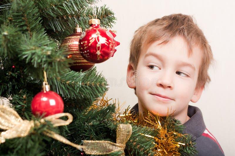 Junge sucht heraus nach dem Weihnachtentreechristmas Baum stockbild