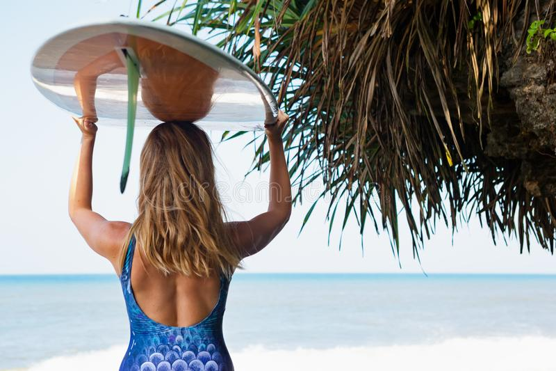 Junge Surferfrau mit Surfbrettweg auf Strand stockfotografie