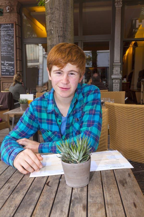 Junge Teenagerjunge mit rotem Haar, die im Freiluftrestaurant sitzen stockbild