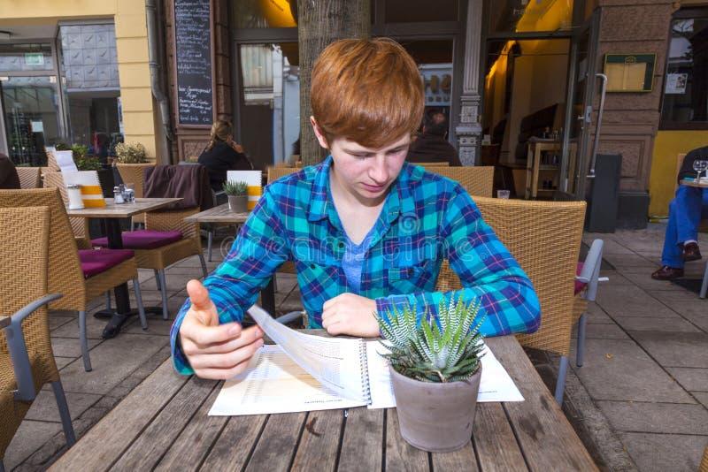 Junge Teenagerjunge mit rotem Haar, die im Freiluftrestaurant sitzen stockfoto