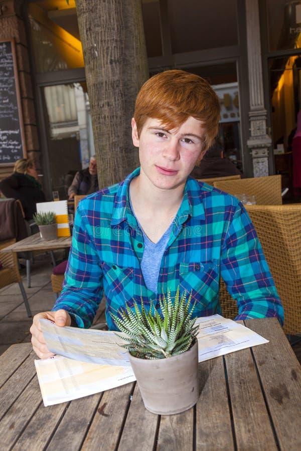 Junge Teenagerjunge mit rotem Haar, die im Freiluftrestaurant sitzen stockbilder