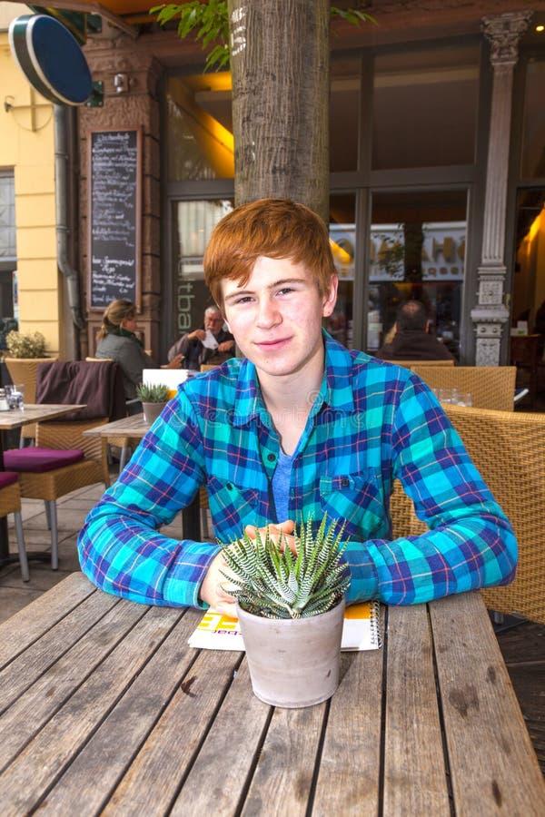 Junge Teenagerjunge mit rotem Haar, die im Freiluftrestaurant sitzen lizenzfreie stockbilder