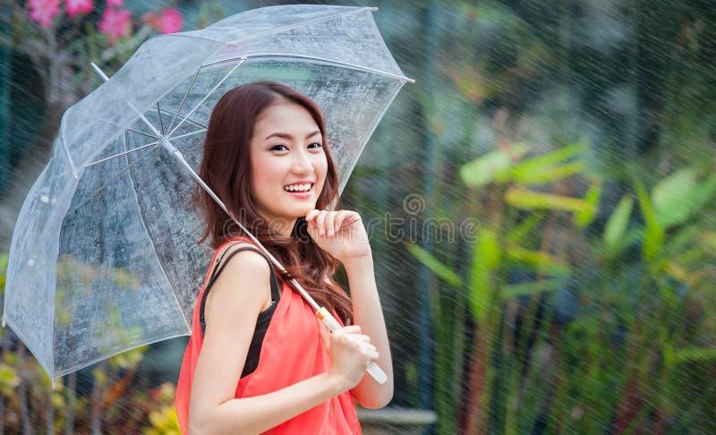Junge thailändische Dame, die mit Unterregenschirm steht lizenzfreie stockbilder