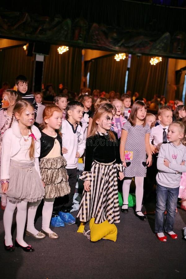 Junge Theaterbesucher Kinder, die enthusiastisch Puppenspieltheater Smeshariki der Kinder Weihnachtsaufpassen stockfotografie
