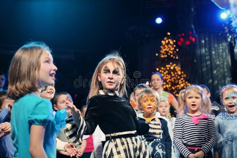 Junge Theaterbesucher Kinder, die enthusiastisch Puppenspieltheater Smeshariki der Kinder Weihnachtsaufpassen stockfoto