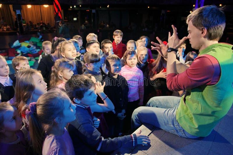 Junge Theaterbesucher Kinder, die enthusiastisch Puppenspieltheater Smeshariki der Kinder Weihnachtsaufpassen lizenzfreie stockbilder