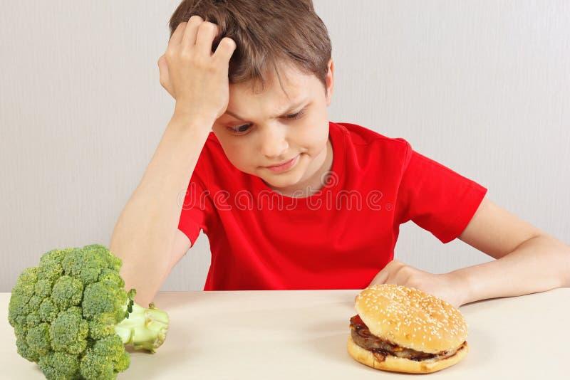 Junge am Tisch wählt zwischen Hamburger und Brokkoli auf weißem Hintergrund lizenzfreies stockfoto