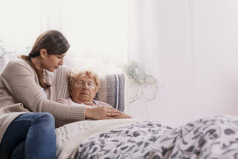 Junge Tochter, welche die kranke Mutter liegt im Krankenhausbett st?tzt stockbild