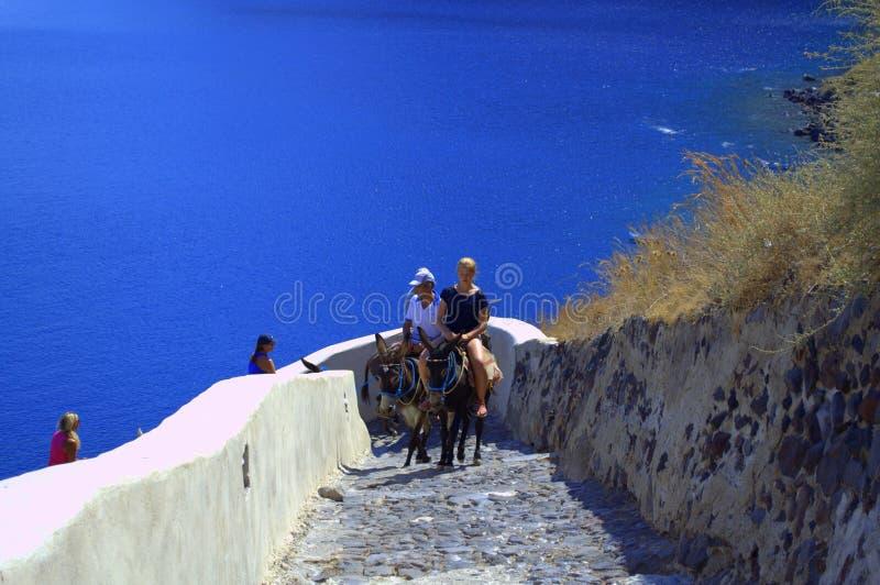 Junge Touristen, die Esel auf griechische Insel reiten lizenzfreies stockbild