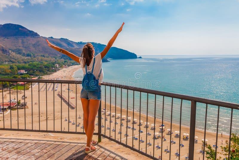 Junge touristische Frau auf dem Strand und der Seelandschaft mit Sperlonga, Lazio, Italien Szenisches Dorf des beliebten Erholung lizenzfreie stockbilder
