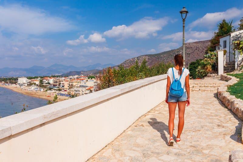 Junge touristische Frau auf dem Strand und der Seelandschaft mit Sperlonga, Lazio, Italien Szenisches Dorf des beliebten Erholung stockfoto