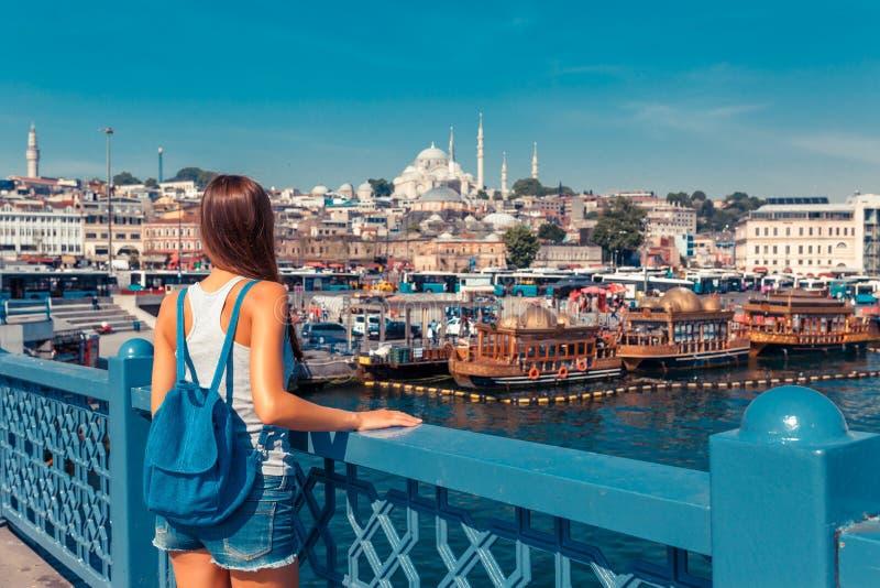 Junge touristische Frau auf Galata-Br?cke, goldene Hornbucht, Istanbul Panoramastadtbild von ber?hmter touristischer Bestimmungso lizenzfreie stockfotografie