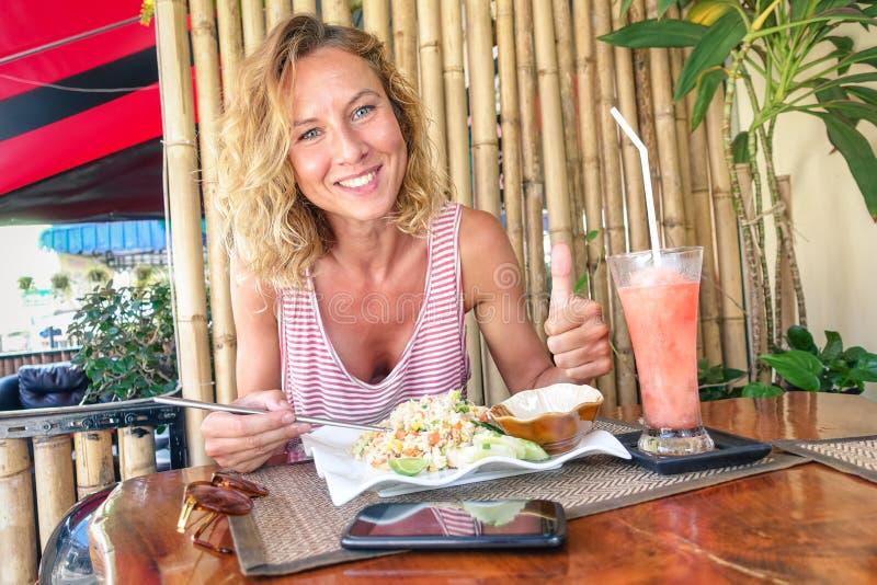 Junge touristische Frau, die gebratenen Reis isst und Fruchterschütterung trinkt stockbild