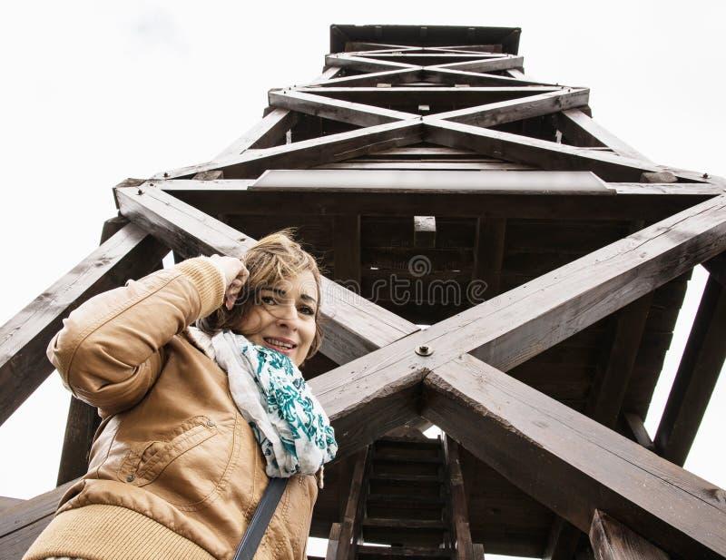 Junge touristische Frau, die unter dem großen hölzernen Ausblickturm aufwirft lizenzfreies stockfoto