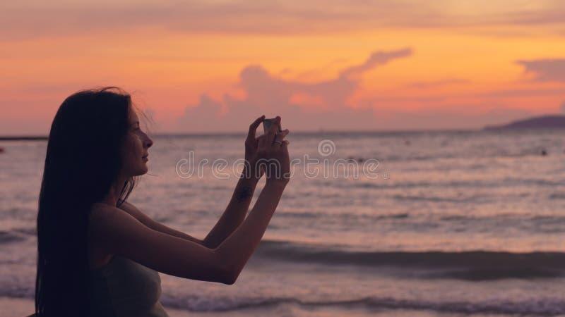 Junge touristische Frau fotografiert Meerblick mit Smartphone während des Sonnenuntergangs am Strand stockfotos