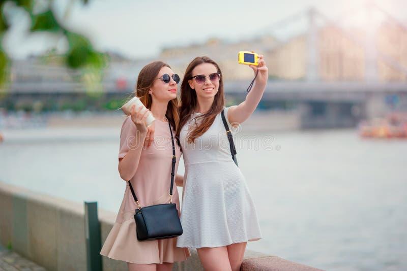 Junge touristische Freunde, die auf draußen lächeln der Feiertage glücklich reisen Kaukasische Mädchen, die selfie Hintergrund gr stockfotos
