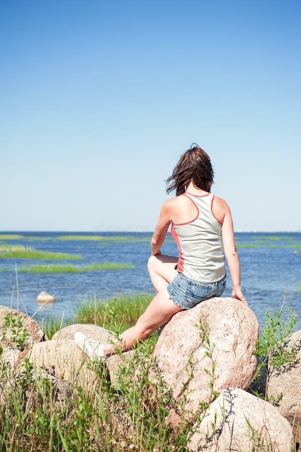 Junge träumende Frau, die auf dem Felsen gegenüberstellt das Meer sitzt lizenzfreies stockbild