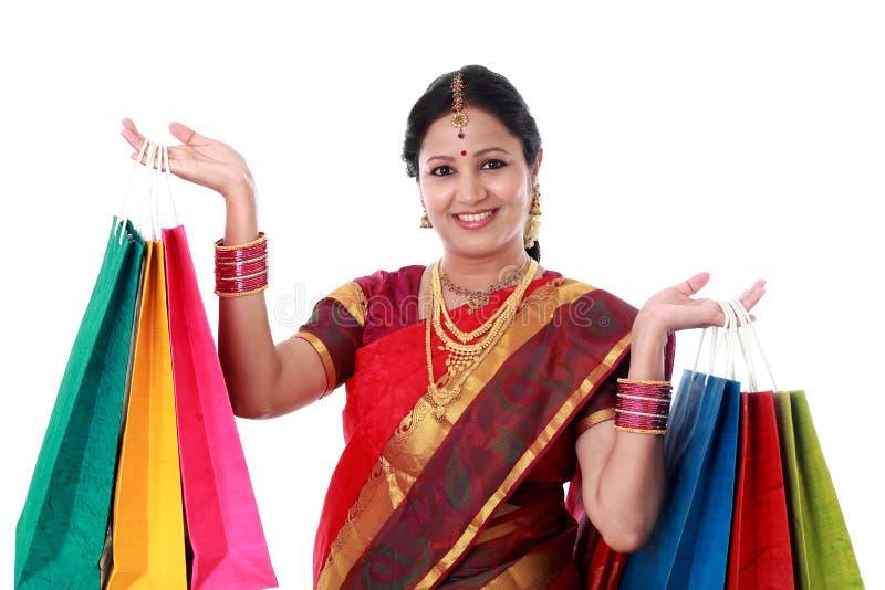 Junge traditionelle indische Frau, die Einkaufstaschen hält lizenzfreie stockbilder