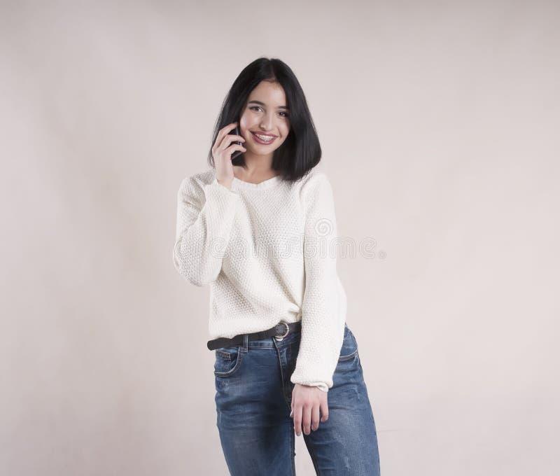 Junge tragende Jeansstrickjacke des schönen Brunettemädchens mit Telefonstudio lizenzfreies stockfoto