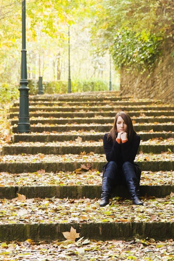 Junge traurige Frau in den Jobstepps lizenzfreie stockfotos