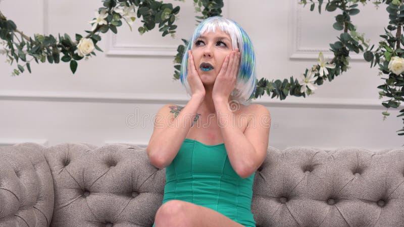 Junge traurige Frau in der Perücke mit Kopfschmerzen ihre Tempel mit Kreisbewegungs-, Gesundheitswesen- und Druckkonzept massiere stockbild