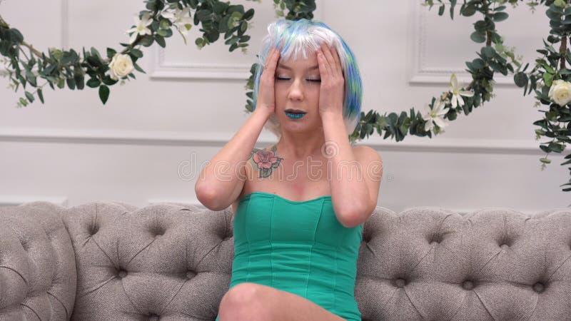 Junge traurige Frau in der Perücke mit Kopfschmerzen ihre Tempel mit Kreisbewegungs-, Gesundheitswesen- und Druckkonzept massiere lizenzfreies stockbild