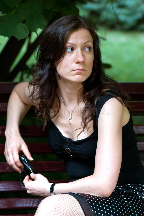 Junge traurige Frau, die draußen sitzt lizenzfreie stockbilder